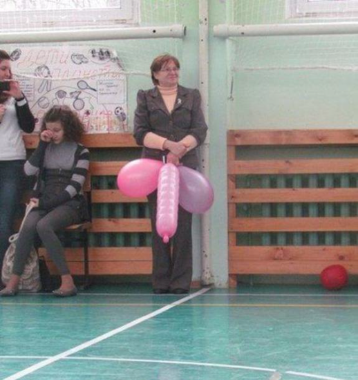 Woman holding balloons in an awkward position
