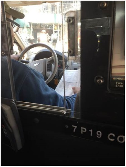 "Great work ethic. Cab driver reading ""Learning to Drive"" while working."